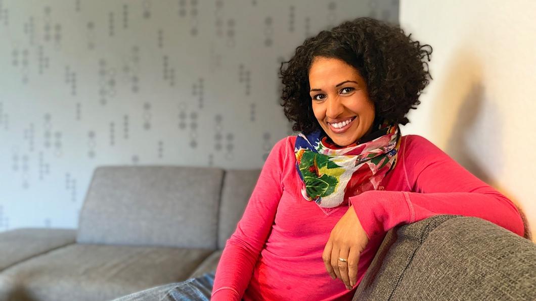 Portrait von Sarah Vecera, die auf einem Sofa sitzt.
